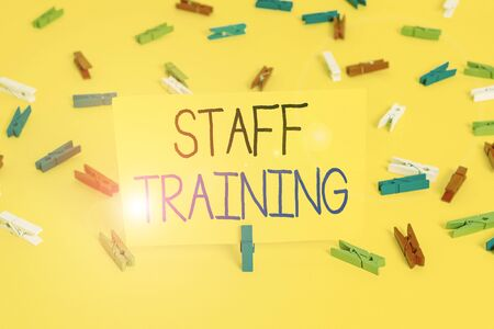Text sign showing Staff Training. Business photo text program that helps employees learn specific knowledge Colored clothespin papers empty reminder yellow floor background office