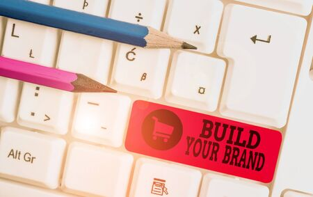 Writing note showing Build Your Brand. Business concept for enhancing brand equity using advertising campaigns White pc keyboard with note paper above the white background