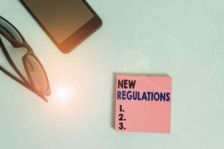 Text sign showing New Regulations Question. Business photo showcasing rules made government order control way something is done Dark eyeglasses colored sticky note smartphone fashion pastel background