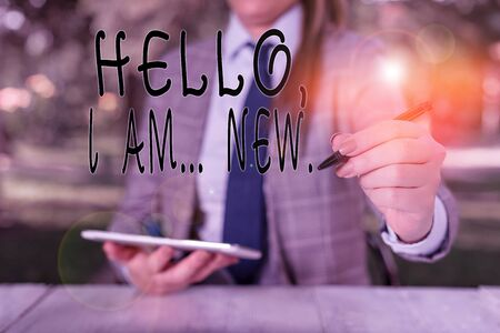 Writing note showing Hello I Am New. Business concept for introducing oneself in a group as fresh worker or student Female business person sitting by table holding mobile phone