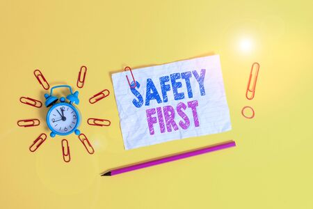 Handwriting text Safety First. Conceptual photo used to say that the most important thing is to be safe Metal alarm clock clips crushed sheet pencil rubber band colored background