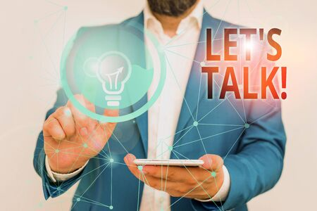 Writing note showing Let S Is Talk. Business concept for suggesting in the beginning of a conversation on the topic Male human wear formal suit presenting using smart device