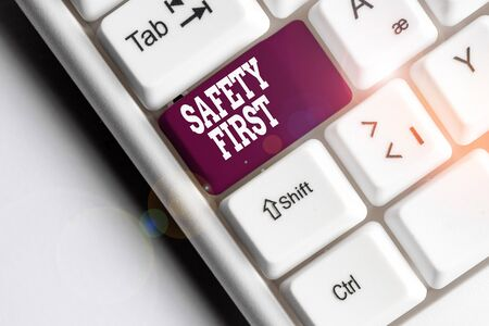 Text sign showing Safety First. Business photo showcasing used to say that the most important thing is to be safe White pc keyboard with empty note paper above white background key copy space