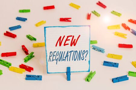 Handwriting text New Regulations Question. Conceptual photo rules made government order control way something is done Colored clothespin papers empty reminder white floor background office