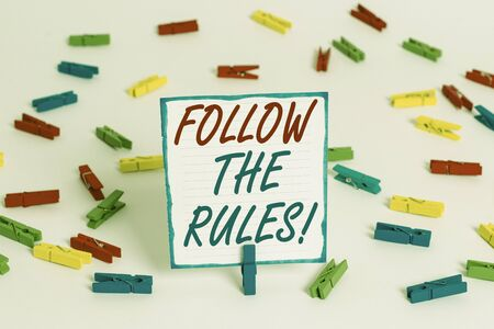 Handwriting text Follow The Rules. Conceptual photo go with regulations governing conduct or procedure Colored clothespin papers empty reminder white floor background office