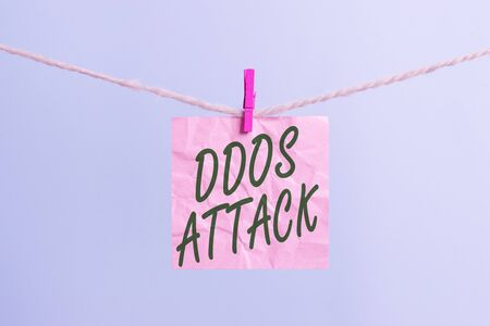 Text sign showing Ddos Attack. Business photo showcasing perpetrator seeks to make a network resource unavailable to user Clothesline clothespin rectangle shaped paper reminder white wood desk