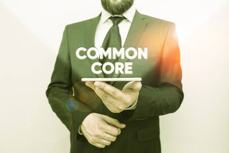 Word writing text Common Core. Business photo showcasing set of academic standards in mathematics and English language Male human wear formal work suit hold smart hi tech smartphone use one hand Stock fotó - 133427110