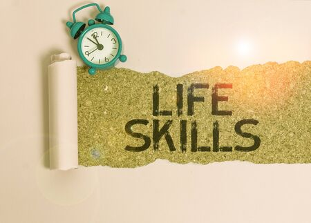 Text sign showing Life Skills. Business photo showcasing skill that is necessary for full participation in everyday life Alarm clock and torn cardboard placed above a wooden classic table backdrop