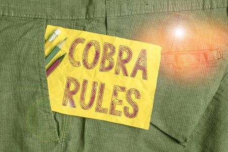 Word writing text Cobra Rules. Business photo showcasing continuing group health insurance coverage after a job loss Writing equipment and yellow note paper inside pocket of man work trousers