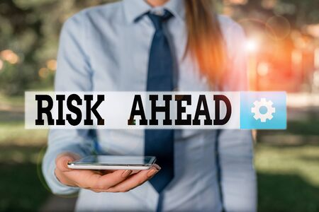 Conceptual hand writing showing Risk Ahead. Concept meaning A probability or threat of damage, injury, liability, loss Business woman in shirt holding laptop and mobile phone Standard-Bild - 133492670