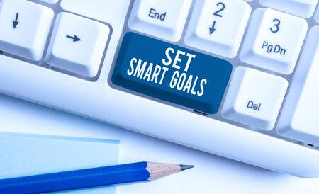 Text sign showing Set Smart Goals. Business photo showcasing giving criteria to guide in the setting of objectives White pc keyboard with empty note paper above white background key copy space