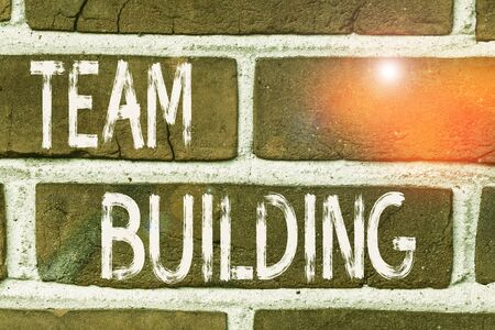 Writing note showing Team Building. Business concept for various types of activities used to enhance social relations Front view red brick wall facade background Old grunge scenery