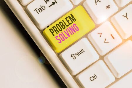 Writing note showing Problem Solving. Business concept for process of finding solutions to difficult or complex issues White pc keyboard with note paper above the white background