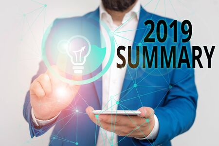 Writing note showing 2019 Summary. Business concept for brief comprehensive especially covering the main points of 2019 Male human wear formal suit presenting using smart device
