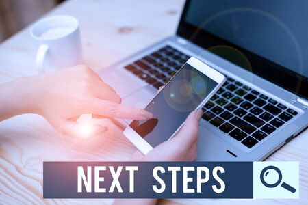 Writing note showing Next Steps. Business concept for something you do or plan after you ve finished something else woman with laptop smartphone and office supplies technology Standard-Bild - 133493355