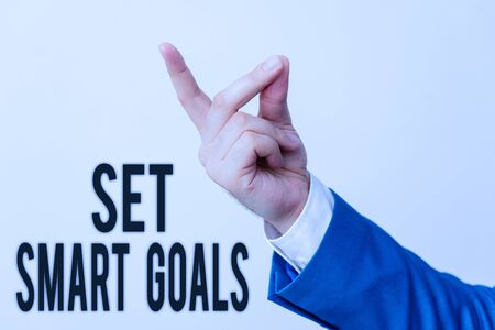 Handwriting text Set Smart Goals. Conceptual photo giving criteria to guide in the setting of objectives Isolated hand pointing with finger. Business concept pointing finger