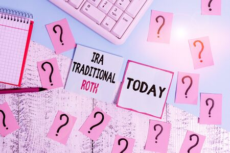 Conceptual hand writing showing Ira Traditional Roth. Concept meaning are tax deductible on both state and federal Writing tools and scribbled paper on top of the wooden table Stock Photo
