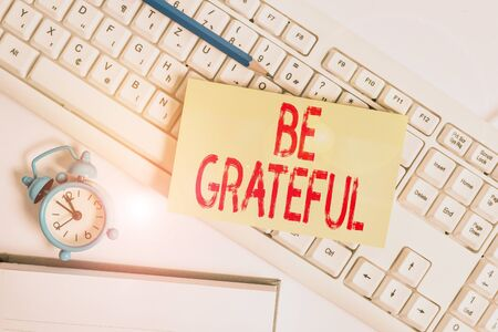 Conceptual hand writing showing Be Grateful. Concept meaning feeling or showing an appreciation for something received Flat lay above empty note paper on pc keyboard pencils and clock