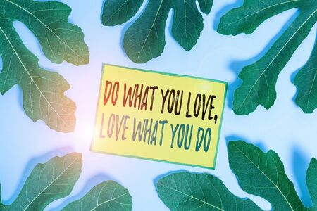 Handwriting text Do What You Love Love What You Do. Conceptual photo you able doing stuff you enjoy it to work in better places then Leaves surrounding notepaper above an empty soft pastel table as background Stok Fotoğraf