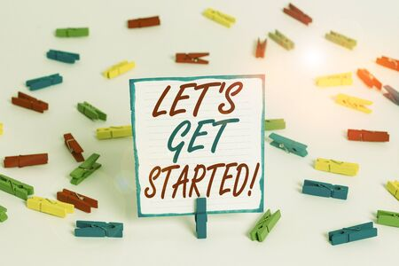 Handwriting text Let S Is Get Started. Conceptual photo to begin doing or working on something you had started Colored clothespin papers empty reminder white floor background office Standard-Bild