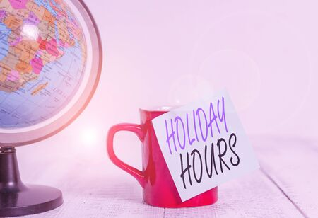 Conceptual hand writing showing Holiday Hours. Concept meaning employee receives twice their normal pay for all hours Globe map coffee cup sticky note lying vintage wooden table