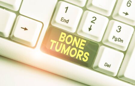 Writing note showing Bone Tumors. Business concept for can be either benign or malignant growths found in the bone White pc keyboard with note paper above the white background