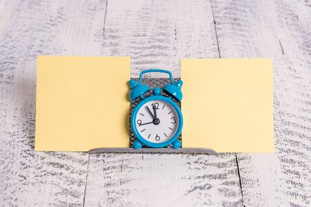 Mini blue alarm clock standing above buffer wire between two notation paper Stockfoto