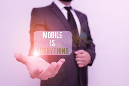 Handwriting text Mobile Is Everything. Conceptual photo Handheld Computer Device a Planner Wallet Organizer Male human with beard wear formal working suit clothes raising one hand up