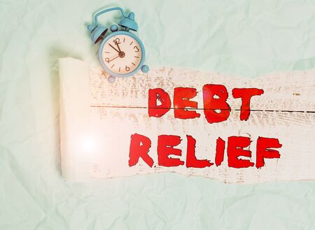 Conceptual hand writing showing Debt Relief. Concept meaning a reduction in the amount of debt that a country has to pay Alarm clock and torn cardboard on a wooden classic table backdrop