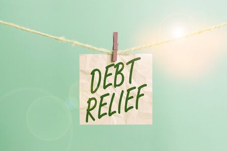 Text sign showing Debt Relief. Business photo showcasing a reduction in the amount of debt that a country has to pay Clothesline clothespin rectangle shaped paper reminder white wood desk