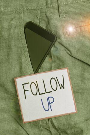 Signo de texto que muestra el seguimiento. Foto de negocios que muestra una continuación de algo que ya se ha iniciado Dispositivo de teléfono inteligente dentro del bolsillo delantero de los pantalones de trabajo formales cerca del papel de nota