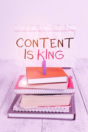 Conceptual hand writing showing Content Is King. Concept meaning believe that content is central to the success of a website pile stacked books notebook pin color reminder white wooden
