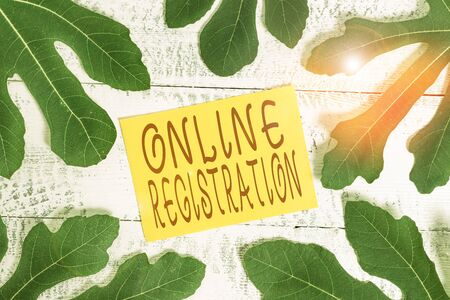 Conceptual hand writing showing Online Registration. Concept meaning System for subscribing or registering via the Internet Leaves surrounding notepaper above a classic wooden table