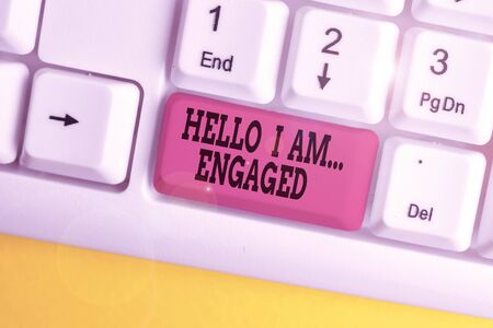 Handwriting text writing Hello I Am Engaged. Conceptual photo He gave the ring We are going to get married Wedding White pc keyboard with empty note paper above white background key copy space