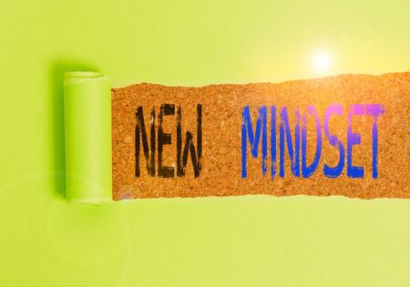 Text sign showing New Mindset. Business photo text Mental attitude or disposition New approach in dealing situation Cardboard which is torn in the middle placed above a wooden classic table