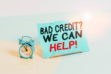 Writing note showing Bad Credit Question We Can Help. Business concept for offering help after going for loan then rejected Alarm clock beside a Paper sheet placed on pastel backdrop