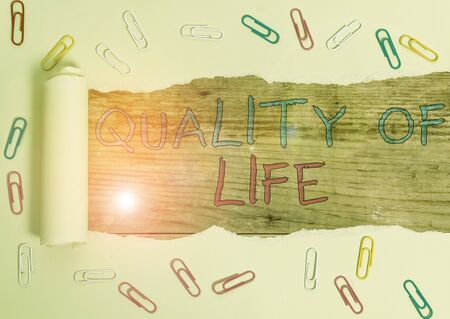 Writing note showing Quality Of Life. Business concept for being in good health decent job Enjoying every moment Paper clip and torn cardboard on wood classic table backdrop