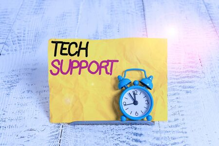 Word writing text Tech Support. Business photo showcasing advising and troubleshooting service provided by a analysisufacturer Mini blue alarm clock stand tilted above buffer wire in front of notepaper Stockfoto