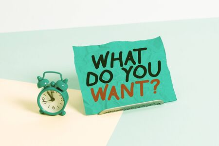 Writing note showing What Do You Want Question. Business concept for say or write in order to ask demonstrating about something Alarm clock beside a Paper sheet placed on pastel backdrop Stock fotó