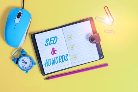 Word writing text Seo And Adwords. Business photo showcasing Pay per click Digital marketing Google Adsense Locked diary sheets clips marker mouse alarm clock colored background