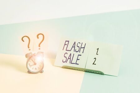 Writing note showing Flash Sale. Business concept for a sale of goods at greatly reduced prices at a short period Alarm clock beside a Paper sheet placed on pastel backdrop