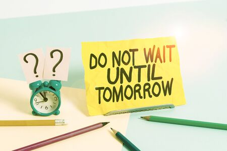 Text sign showing Do Not Wait Until Tomorrow. Business photo text needed to do it right away Urgent Better do now Mini size alarm clock beside stationary placed tilted on pastel backdrop Foto de archivo
