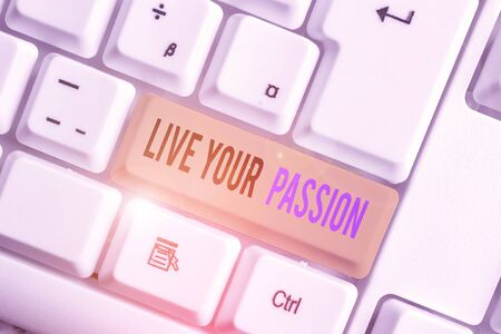 Text sign showing Live Your Passion. Business photo text Doing something you love that you do not consider a job White pc keyboard with empty note paper above white background key copy space Фото со стока