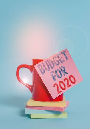 Conceptual hand writing showing Budget For 2020. Concept meaning An written estimates of income and expenditure for 2020 Coffee cup colored sticky note stacked pads plain background Archivio Fotografico