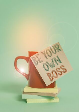 Conceptual hand writing showing Be Your Own Boss. Concept meaning Entrepreneurship Start business Independence Selfemployed Coffee cup colored sticky note stacked pads plain background