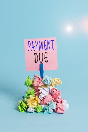 Text sign showing Payment Due. Business photo showcasing The date when payment should be received by the company Reminder pile colored crumpled paper clothespin reminder blue background