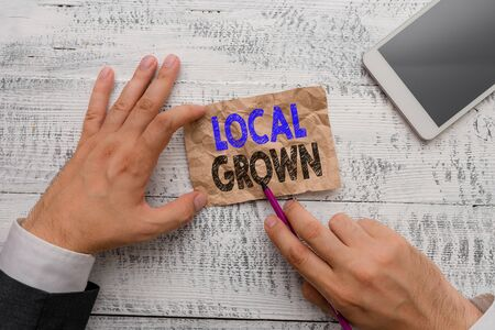 Conceptual hand writing showing Local Grown. Concept meaning agricultural products produced then sold within a certain area Hand hold note paper near writing equipment and smartphone