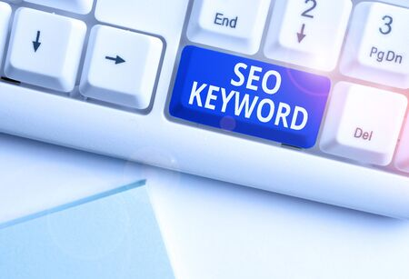 Conceptual hand writing showing Seo Keyword. Concept meaning phrases in your web content that help showing find your site White pc keyboard with note paper above the white background