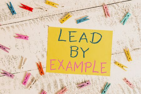 Conceptual hand writing showing Lead By Example. Concept meaning Be a mentor leader follow the rules give examples Coach Colored clothespin rectangle shaped paper blue background
