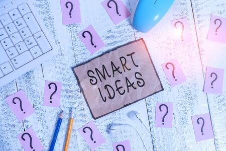 Conceptual hand writing showing Smart Ideas. Concept meaning A thought or collection of thoughts that generate in the mind Writing tools and scribbled paper on top of the wooden table Stock Photo